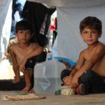 Due fratellini in un accampamento allestito accanto a un'autostrada, nella parte ovest di Aleppo (Siria) per accogliere migliaia di sfollati dalla zona est della città - ©UNICEF/UN027713/Al-Issa